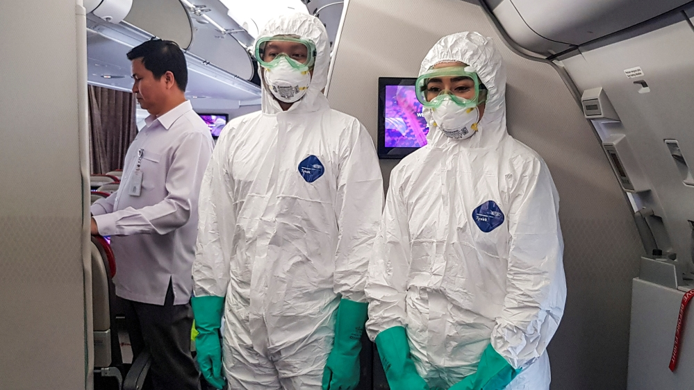 Officers wearing protective suits are seen in Batik Airplane before take-off to pickup Indonesian citizens at Wuhan, in Soekarno-Hatta International Airport