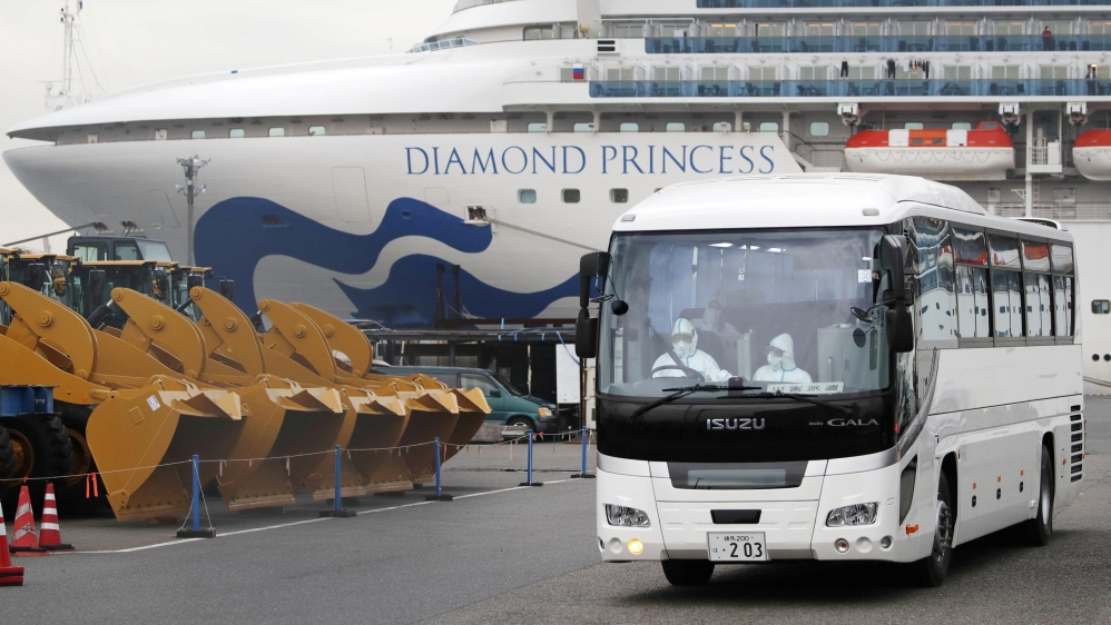 A driver wearing protective suits is seen inside a bus which believed to carry elderly passengers of the cruise ship Diamond Princess, where dozens of passengers were tested positive for coronavirus,