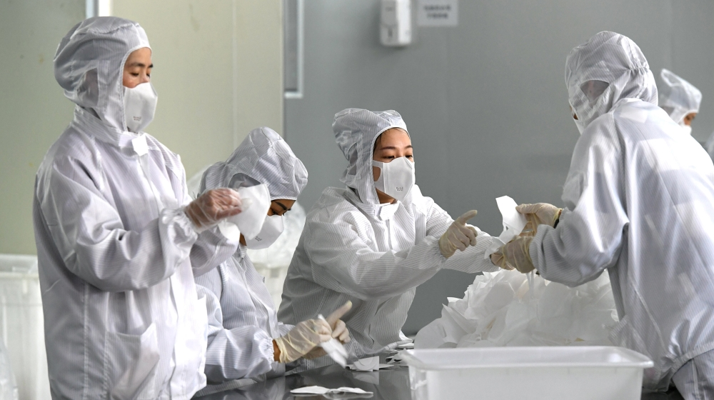 Employees work on a production line manufacturing face masks at a factory, as the country is hit by an outbreak of the novel coronavirus, in Fuzhou, Fujian province, China February 15, 2020. cnsphoto
