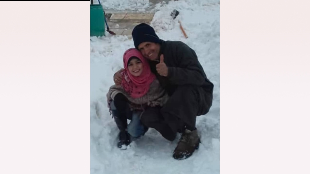 Mustafa Hamadi and his daughter Huda pose in the snow a day before they were killed by carbon monoxide inhalation in Killi, Idlib province