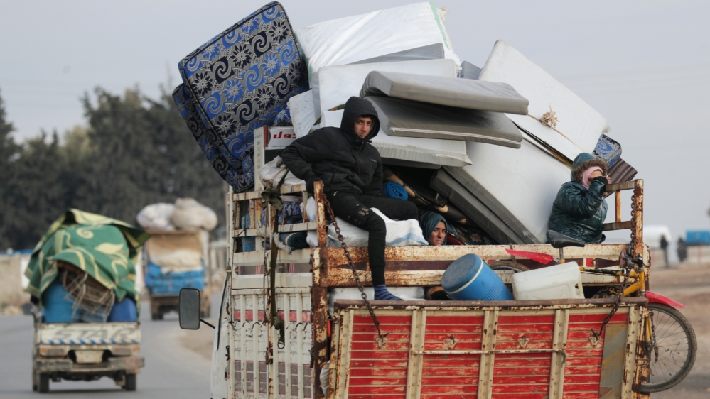 Internally displaced people ride on a pick up truck with their belongings in Azaz