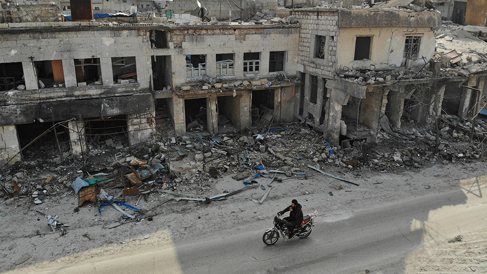 An aerial view taken on February 19, 2020 shows a man riding his motorcycle past destroyed buildings in the Syrian town of Ihsim in the southern countryside of Idlib. (Photo by Omar HAJ KADOUR / AFP)