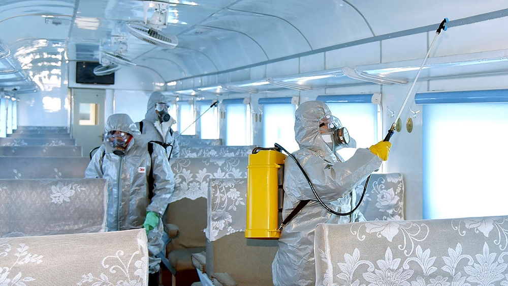 This undated picture released from North Korea's official Korean Central News Agency (KCNA) on February 15, 2020 shows people in protective suits spraying disinfectant at an undisclosed location in No