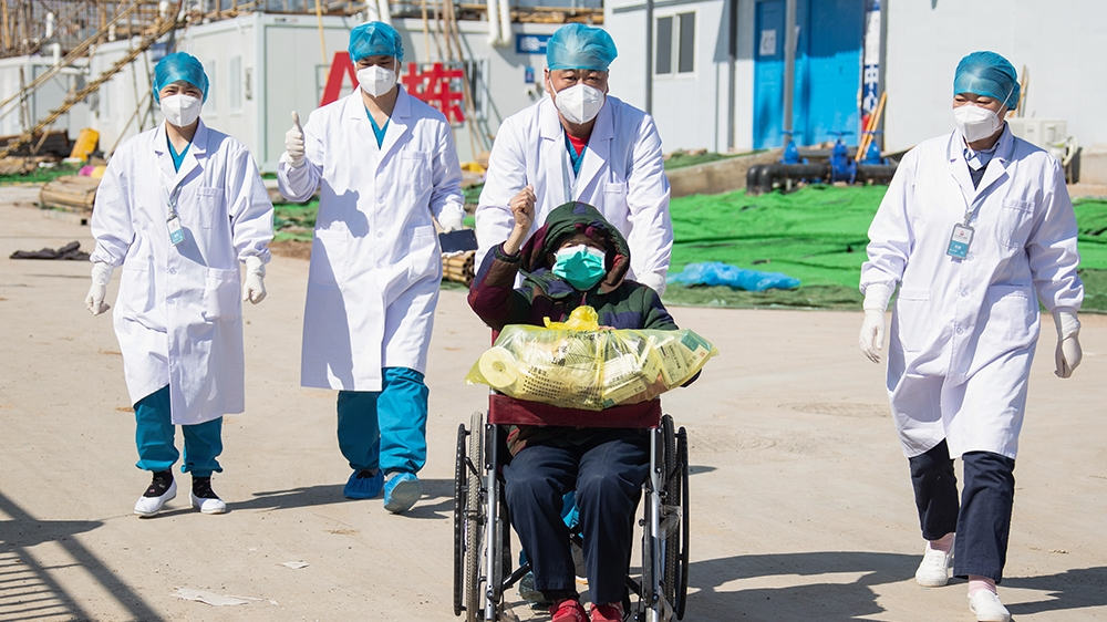 A recovered patient (C in wheelchair), 83, is discharged from Leishenshan Hospital, the newly-built makeshift hospital for novel coronavirus patients, in Wuhan in China's central Hubei province on Feb
