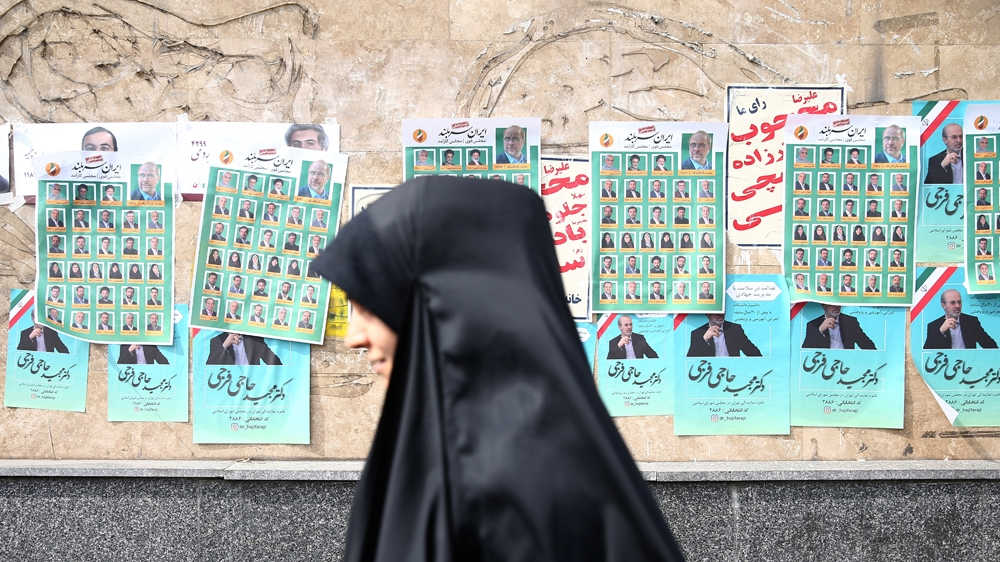 A woman walks past parliamentary election campaign posters in T