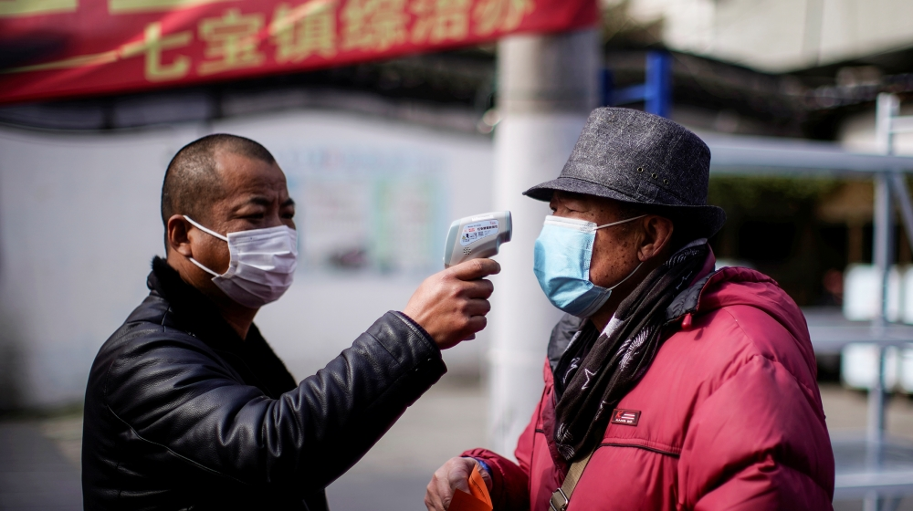 A man checks the temperature on a street in Qibao, an old river town on the outskirts of Shanghai, China, as the country is hit by an outbreak of the novel coronavirus, February 19, 2020. Picture take