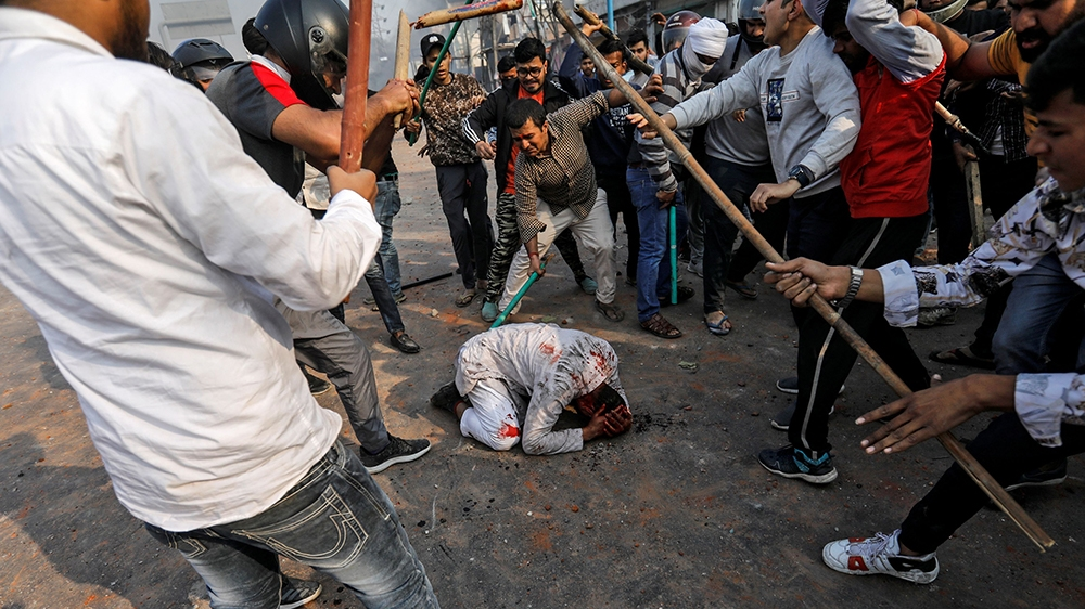 SENSITIVE MATERIAL. THIS IMAGE MAY OFFEND OR DISTURB    People supporting the new citizenship law beat a Muslim man during a clash with those opposing the law in New Delhi, India, February 24, 2020. R