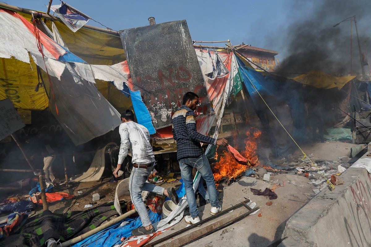 CAA supporters destroy the protest site used by those opposing it in New Delhi. Police on Monday imposed an emergency law prohibiting any gatherings in the violence-hit areas. [Danish Siddiqui/Reuters]