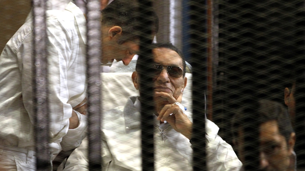 A file photo dated 13 April 2013 shows Gamal Mubarak (L) and brother Alaa Mubarak (R), with their father former Egyptian President Hosni Mubarak in a cage inside the court room during his trial at the