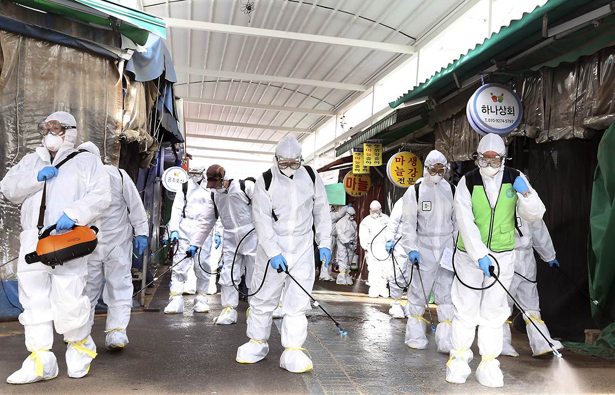 Workers spray disinfectant as a precaution against the coronavirus at a market in Bupyeong, South Korea. [Lee Jong-chul/Newsis/AP]