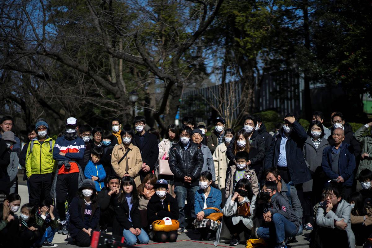 Njerëzit të veshur me maska mbrojtëse janë parë në parkun Ueno pas një shpërthimi të koronavirusit të romanit, në Tokio, Japoni.  [Athit Perawongmetha / Reuters]