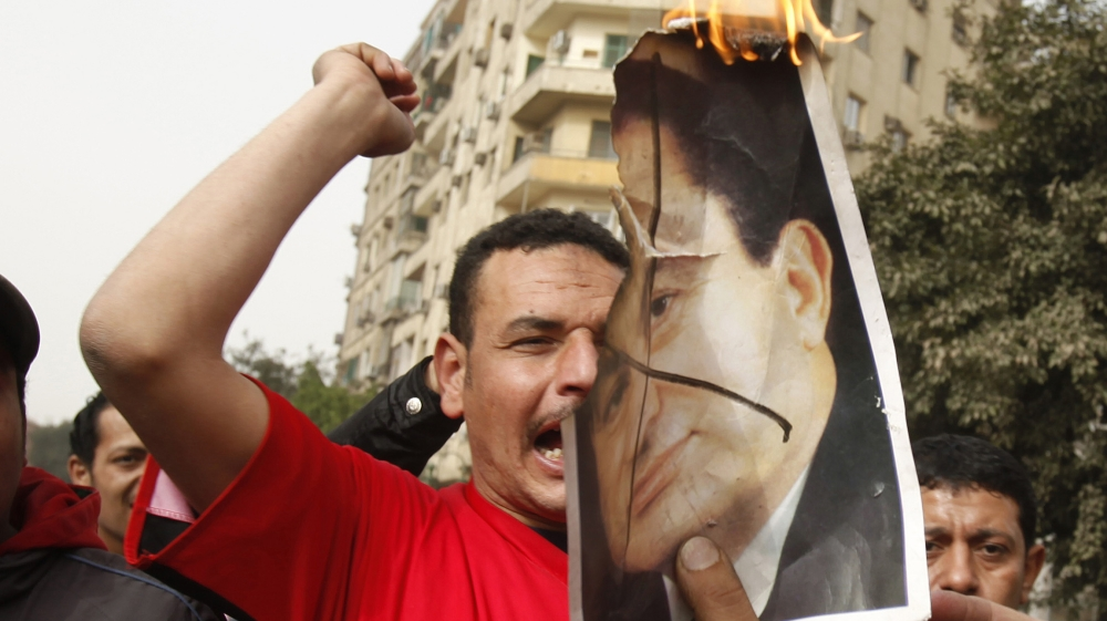 Protesters burn a picture of President Hosni Mubarak as they shout anti-goverment slogans during a demonstration in Cairo January 29, 2011. Thousands of angry Egyptians rallied in central Cairo on Sat