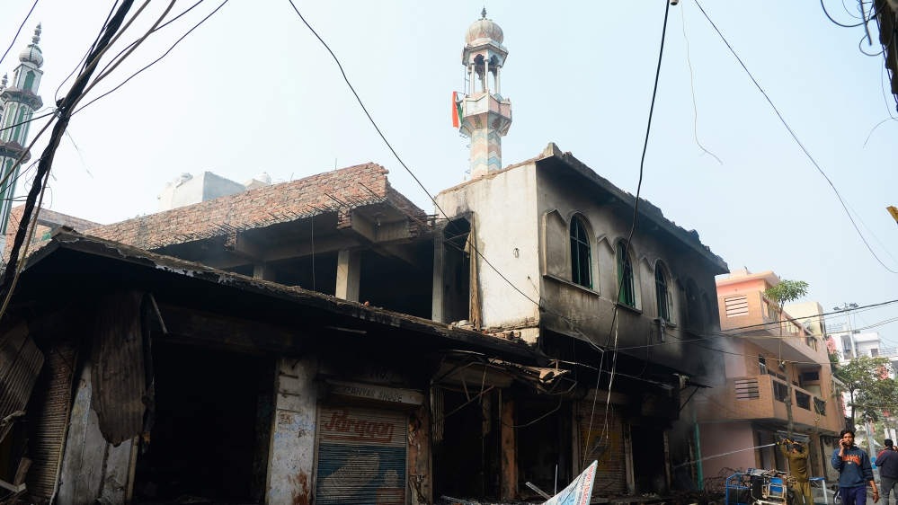 A man (R) speaks on his mobile phone as he walks past a burnt-out mosque and shops following clashes between people supporting and opposing a contentious amendment to India's citizenship law, in New D