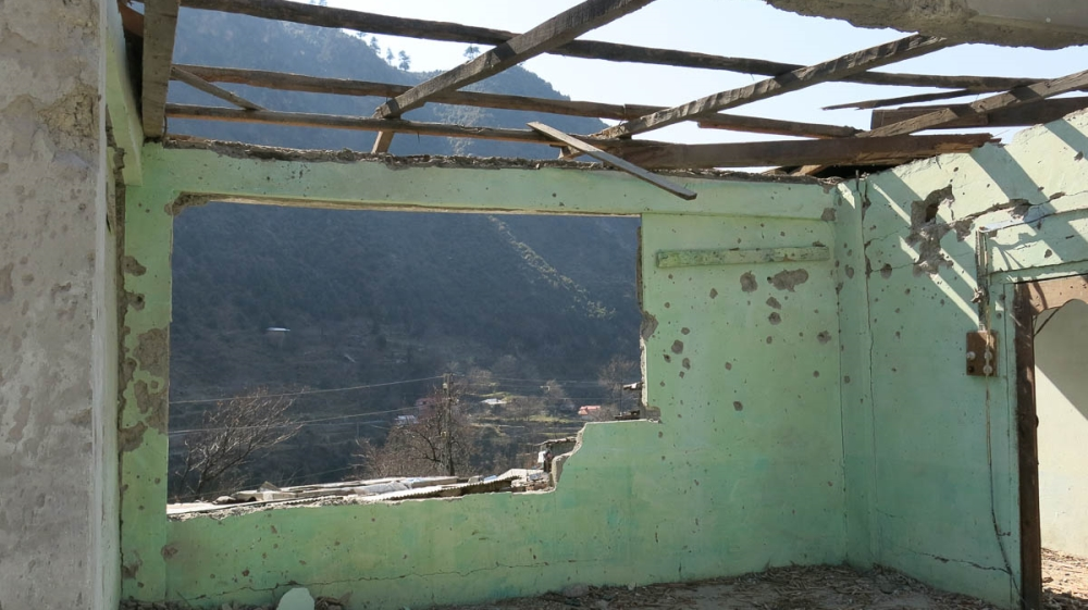 The remains of Muhammmad Siddiq Mir's destroyed living room, looking out upon the Neelum river [Asad Hashim/Al Jazeera]