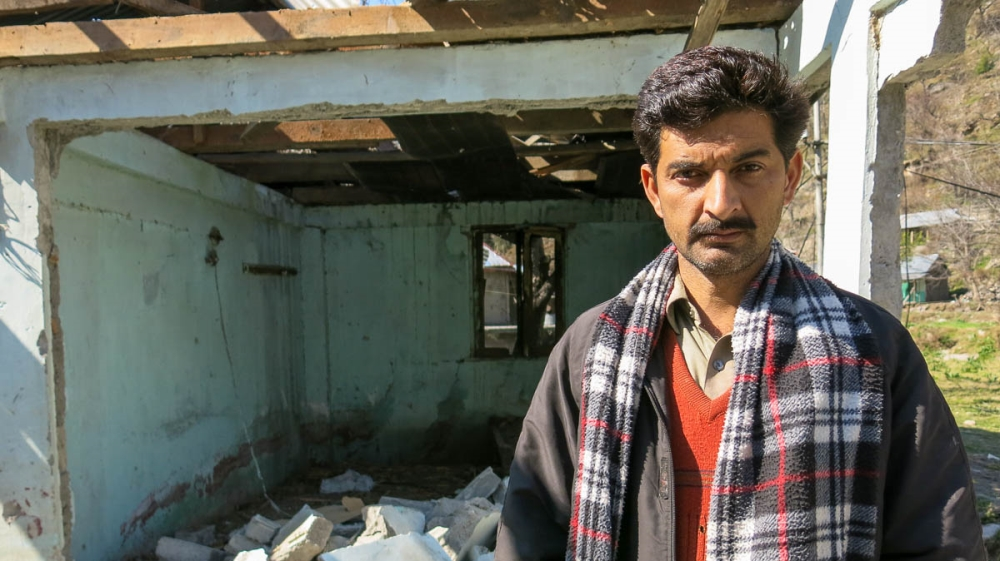 Muhammad Siddiq Mir, 30, stands amid the rubble of his home, destroyed by Indian artillery firing across the Line of Control into the Pakistan-administered Kashmir village of Jura. [Asad Hashim/Al Jaz