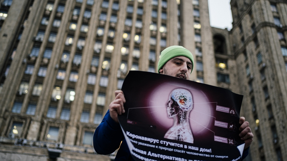 An environmental activist pickets in front of the Russian Foreign Ministry headquarters demanding a thorough screening of passengers arriving from Southeast Asia to protect against
