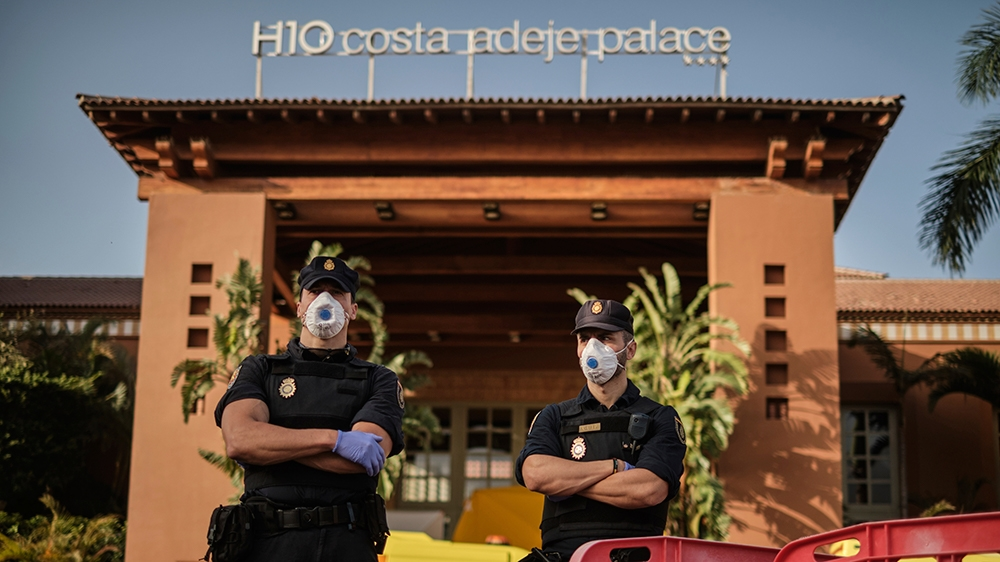 Police officers wearing masks stand in front of the H10 Costa Adeje Palace hotel in La Caleta, in the Canary Island of Tenerife, Spain, Wednesday, Feb. 26, 2020. Spanish officials say a tourist hotel