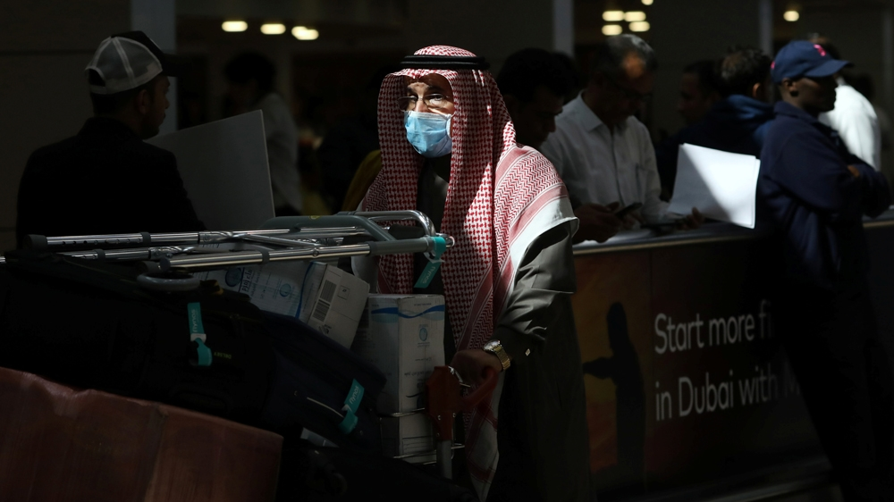 A traveller wears a mask as he pushes a cart with luggage at the Dubai International Airport, after the UAE's Ministry of Health and Community Prevention confirmed the country's first case