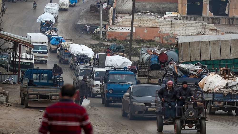 A convoy of trucks transporting Syrians and their belongings drives through the village of al-Mastuma, in the northern countryside of Syria's Idlib province on January 30, 2020, as thousands of people