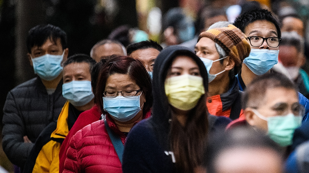 People wearing facemasks as a preventative measure following a coronavirus outbreak which began in the Chinese city of Wuhan, line up to purchase face masks from a makeshift stall after queueing for h
