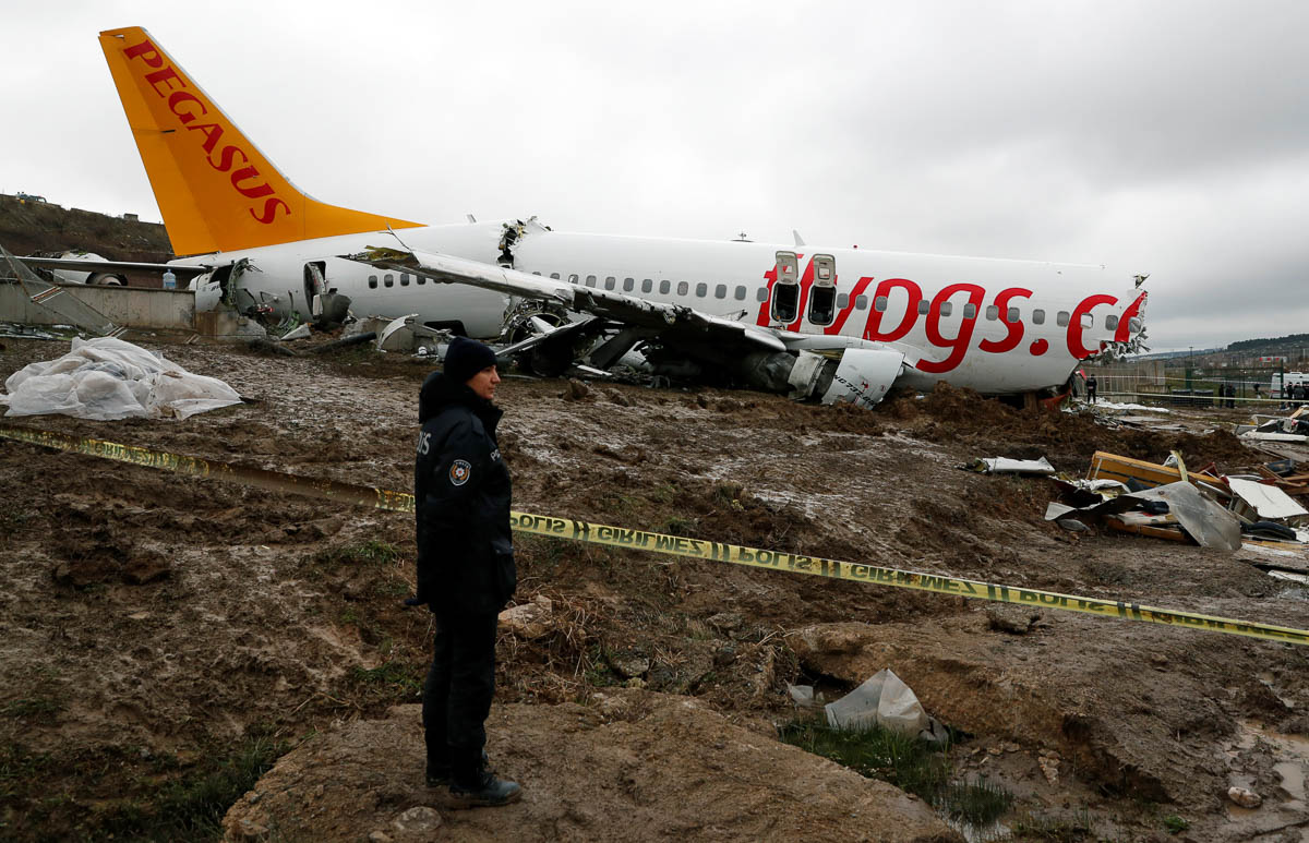 A police officer stands near the Pegasus Airlines Boeing 737-86J plane wreckage after it overran the runway during landing at Istanbul's Sabiha Gokcen airport. [Murad Sezer/Reuters]