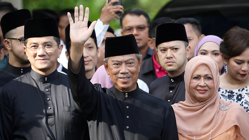 Malaysia's Prime Minister Designate and former interior minister Muhyiddin Yassin waves to reporters before his inauguration as the 8th prime minister, outside his residence in Kuala Lumpur, Malaysia,