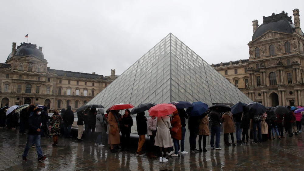 People line up at the Louvre Museum as the staff closed the museum during a staff meeting about the coronavirus outbreak, in Paris