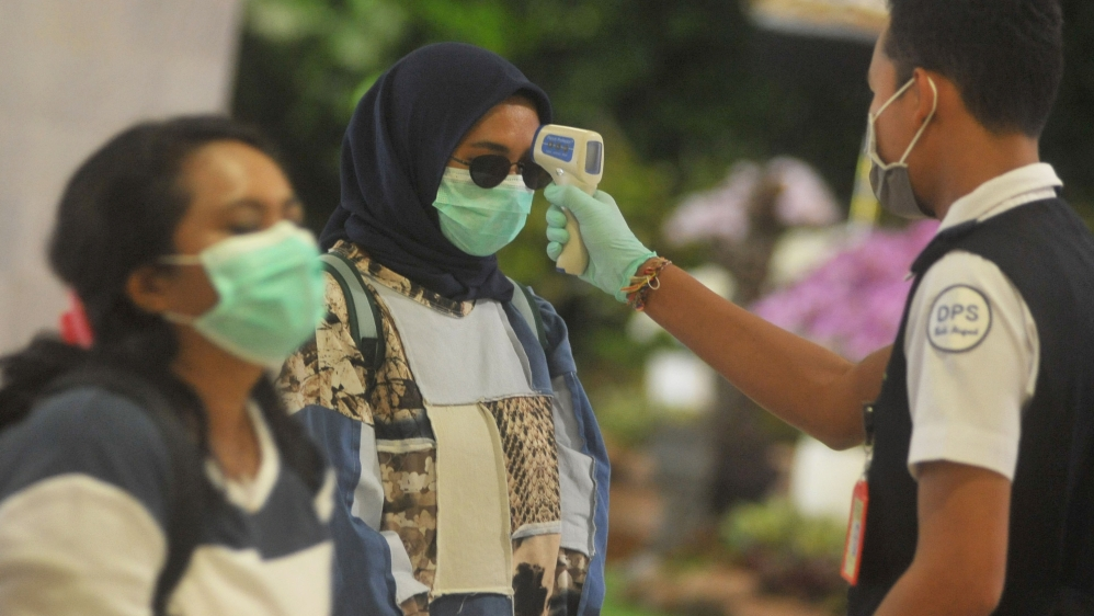 An officer uses a thermal scanner in I Gusti Ngurah Rai International airport after Indonesia confirmed new cases of coronavirus disease (COVID-19) in Denpasar, Bali