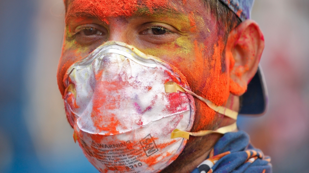 A man wearing protective mask attends Holi celebrations amid coronavirus precautions India