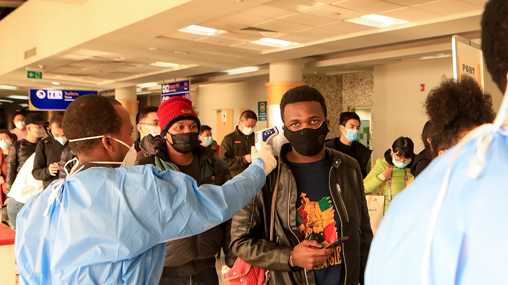 epa08291220 (FILE) - Kenyan health workers screening passengers wearing face masks after they arrived from China, at Jomo Kenyatta International Airport in Nairobi, Kenya, 29 January 2020 (reissued 13