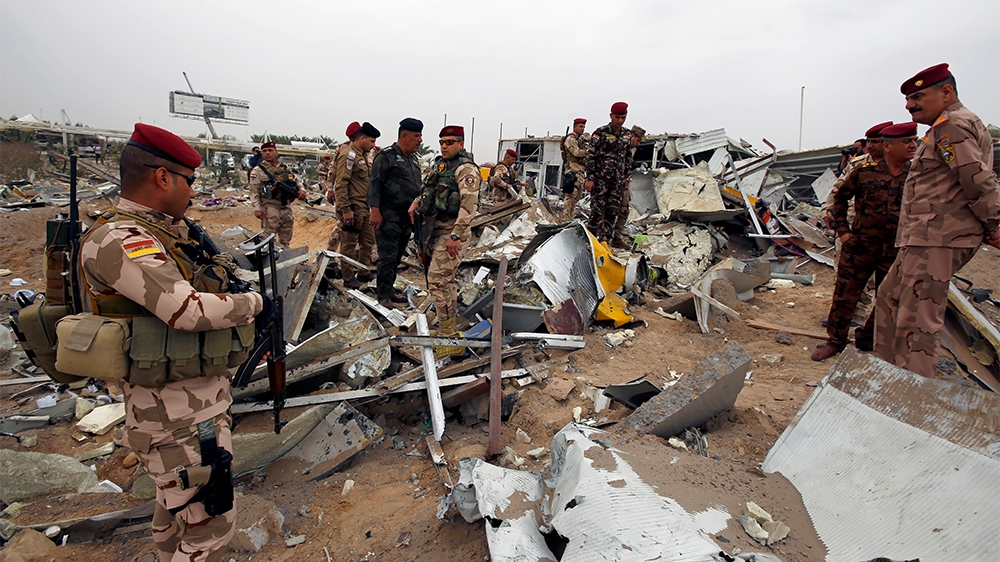Members of Iraqi security forces check the damages a civilian airport under construction which, according to Iraqi religious authorities, was hit by a U.S. air strike, in the holy Shi'ite city of Kerb