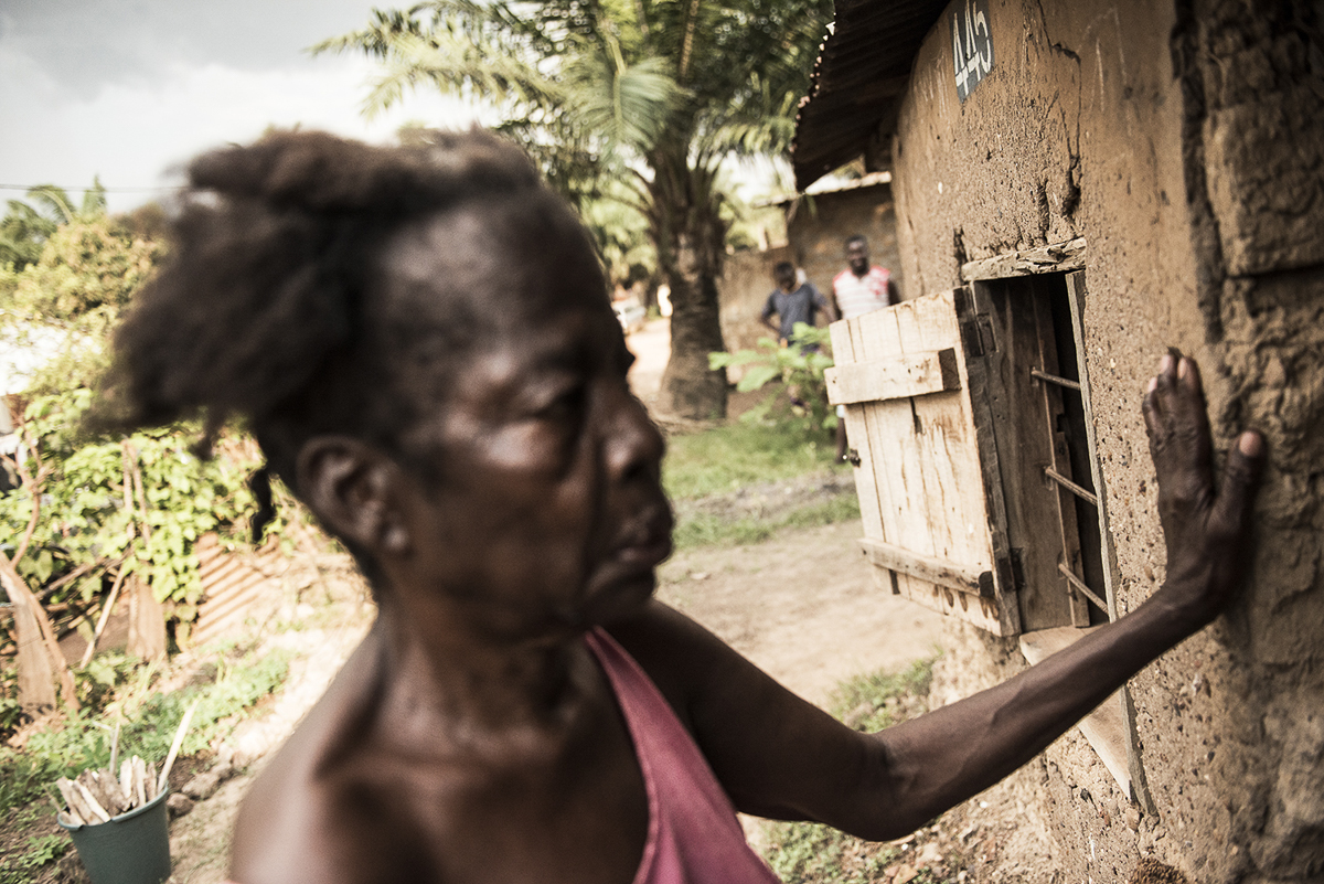 Martine Rengapou rushes into her house in Bangui as people outside yell at her. She never ventures far from her home and knows that, since she has been accused of witchcraft, to do so could result in her being killed. She has been abandoned by her family and now lives alone. [Ugo Lucio Borga/Al Jazeera]