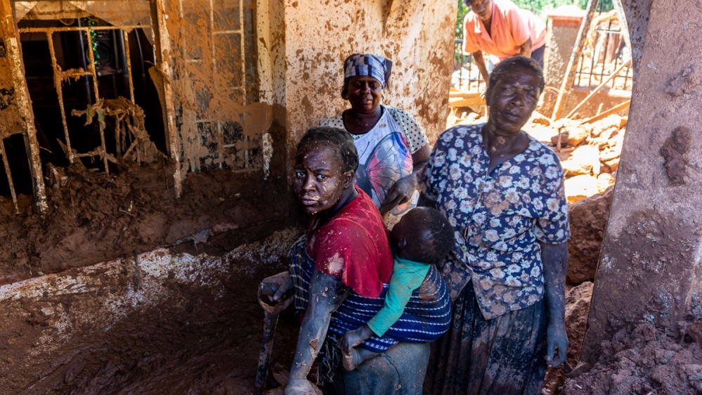 Women in Chimanimani's Ngangu township scoop up mud from their home after mudfalls from Cyclone Idai swept through the hillside neighbourhood. [Tendai Marima/Al Jazeera]