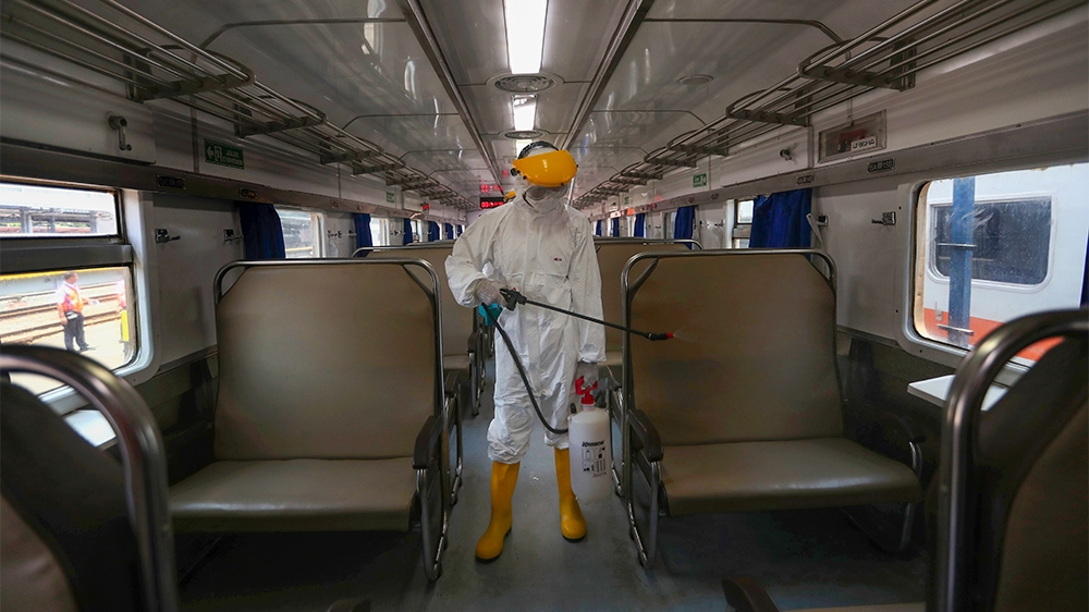 An employee in protective gears sprays disinfectant in the wake of coronavirus outbreak inside a train at the Senen train station in Jakarta Indonesia, Sunday, March 15, 2020. Indonesia's capital city