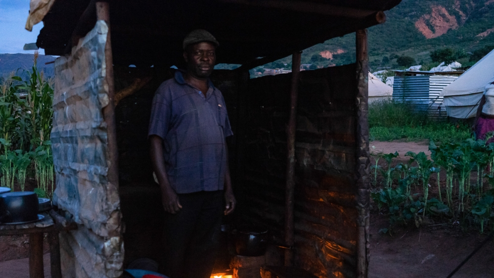 Godfrey Muparingwe in a makeshift kitchen where he and his family prepare meals. [Tendai Marima/Al Jazeera]