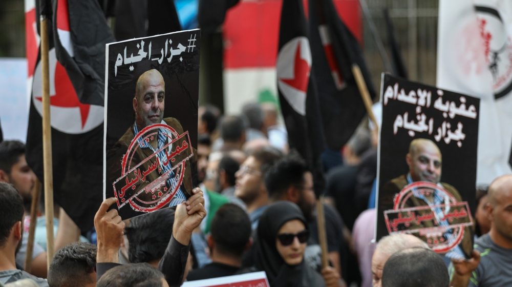 Former detainees of the pro-Israel South Lebanon Army (SLA) militia hold posters depicting former SLA member Amer al-Fakhoury during a demonstration denouncing his return and entry outside the Justice
