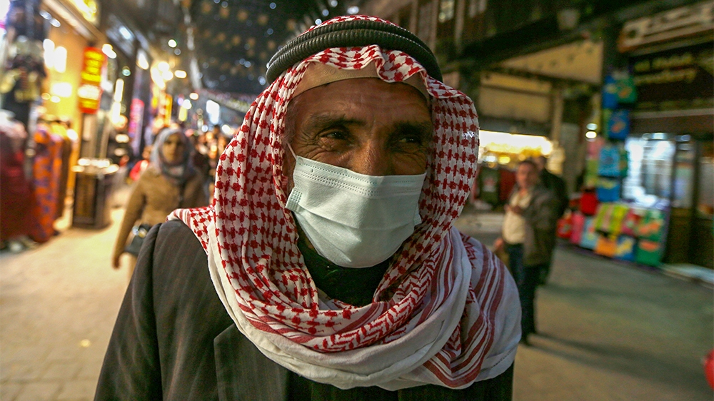 A Syrian man wearing a mask walks at the Hamidiya market in the capital Damascus' old sector on March 15, 2020. - Even though no cases of coronavirus Covid-19 have yet been reported in the city, some