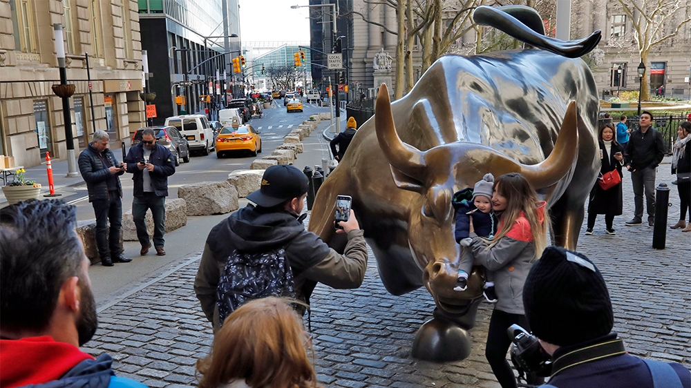 People pose for photos with the Charging Bull statue in New York's Financial District, Sunday, March 15, 2020. New York Gov. Andrew Cuomo Cuomo said Saturday that more than 600 New Yorkers have been d
