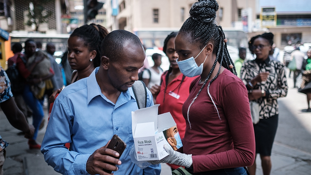A woman sells face masks for 200 Kenyan shillings (about 2 USD) per piece, on a street, as a preventative measure, in downtown of Nairobi, Kenya, on March 16, 2020. - Kenya on March 13, 2020, announce