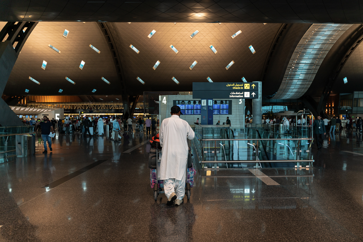 People at the departure terminal at Hamad International Airport. All incoming flights have been suspended for a preliminary two-week period. [Sorin Furcoi/Al Jazeera]