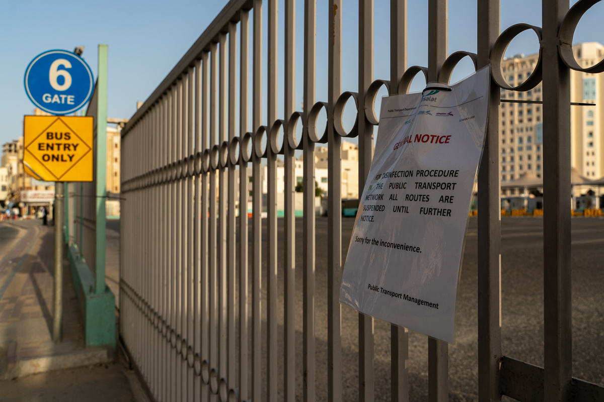 The gate of a terminal for public buses displays a sign informing people that all public transport has been suspended for disinfection until further notice. [Sorin Furcoi/Al Jazeera]