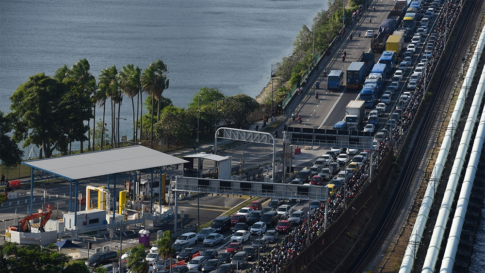 Vehicles form a long queue to enter Woodlands checkpoint in Singapore on March 17, 2020 from across the causeway of the southern Malaysian state of Johor. - Malaysia will ban its citizens from travell