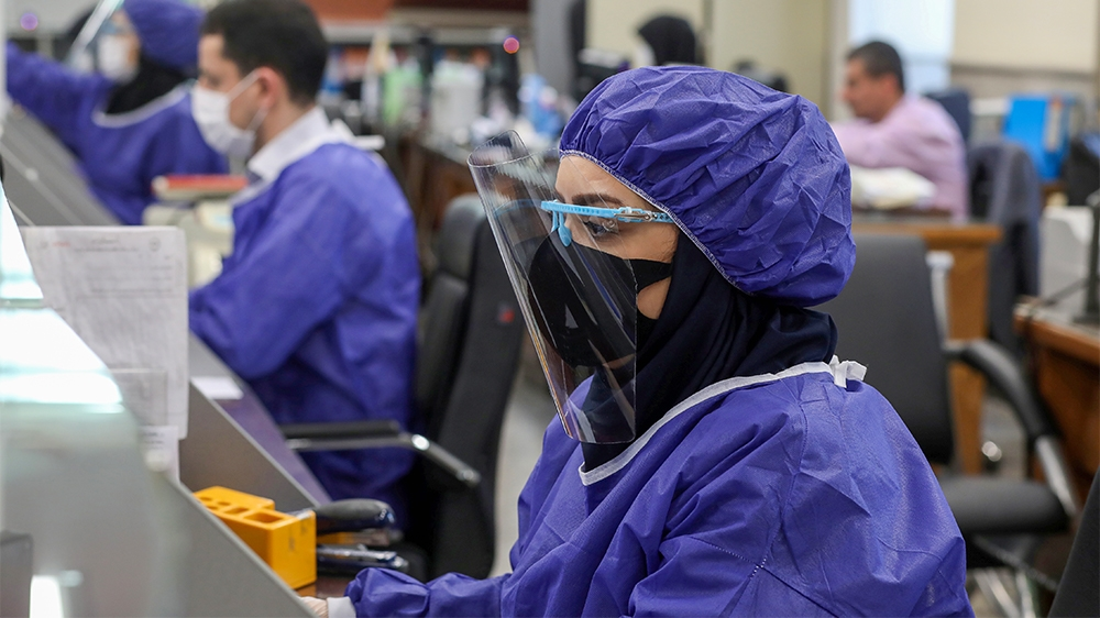 Bank employees wear protective face masks and clothes, following the outbreak of coronavirus, during the work in Tehran, Iran March 17, 2020. WANA (West Asia News Agency)/Ali Khara via REUTERS ATTENTI