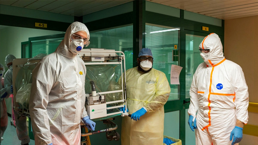 Medical workers in protective suits transfer a coronavirus patient from the intensive care unit of the Gemelli Hospital to the Columbus Covid Hospital, which has been assigned as one of the new corona