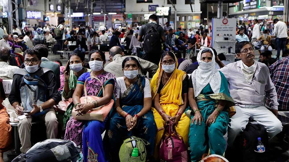 Indians waiting at a train station wear protective masks as a precaution against a new virus outbreak in Mumbai, India, Tuesday, March 17, 2020. For most people, the new coronavirus causes only mild o