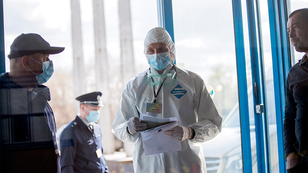 epa08294434 Customs officers wear protective masks as they control the cars of passengers arriving at the Leuseni Custom, Moldova, 14 March 2020. Moldova closes some border crossings with Romania aft