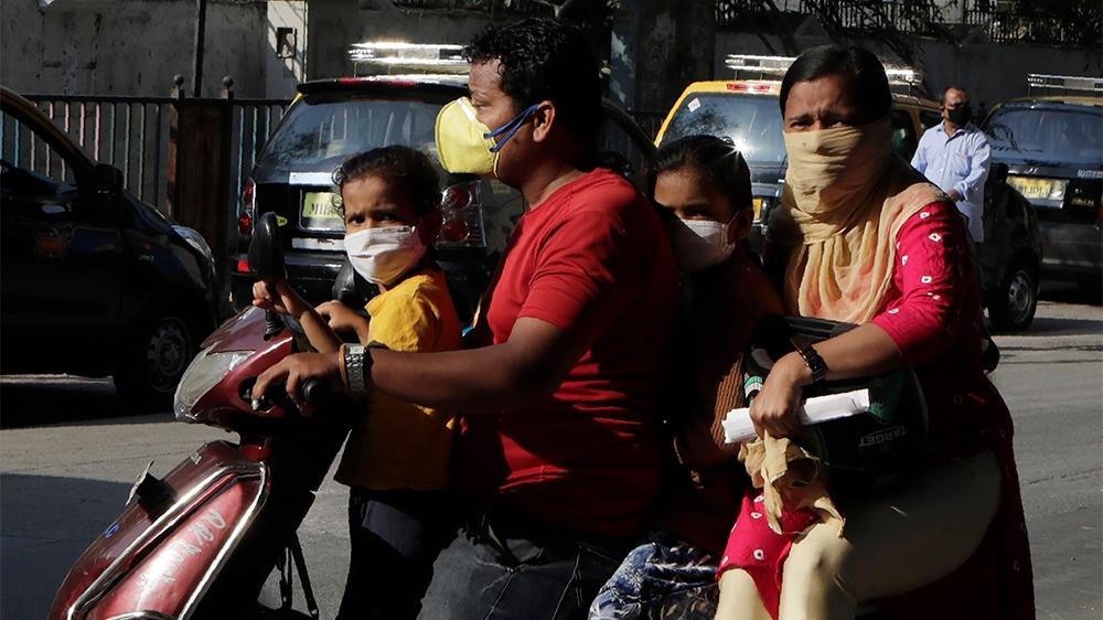 People wear protective masks as a precautionary measure following the Coronavirus pandemic in Mumbai, India, Tuesday, March 17, 2020. (AP Photo/Rajanish Kakade)