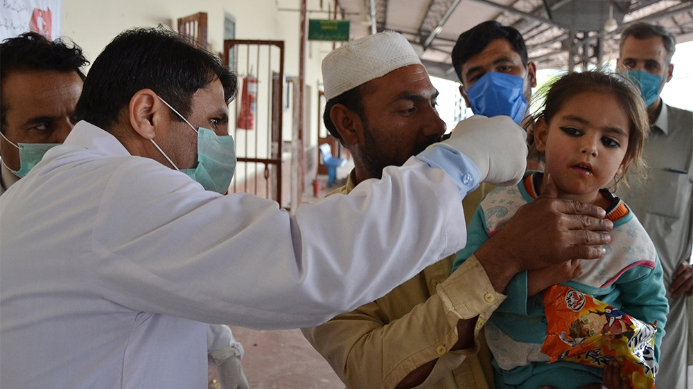 A man holds his daughter as a health official checks her body temperature amid concerns over the spread of the COVID-19 novel coronavirus at Peshawar railway station in Peshawar on March 17, 2020. (Ph