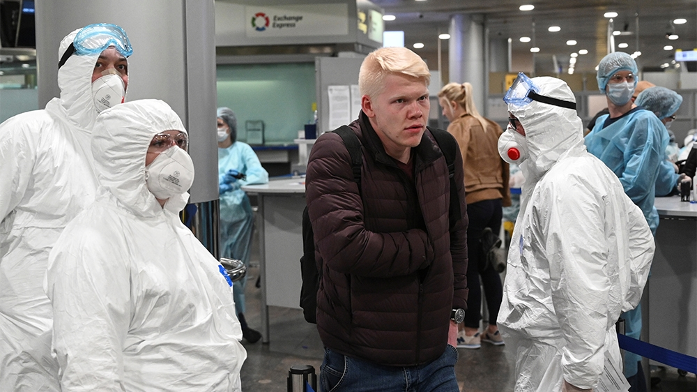 Russian officials and medical staff wearing protective gear check passengers as a preventive measure against the coronavirus (COVID-19) at Sheremetyevo International Airport outside Moscow, Russia Mar