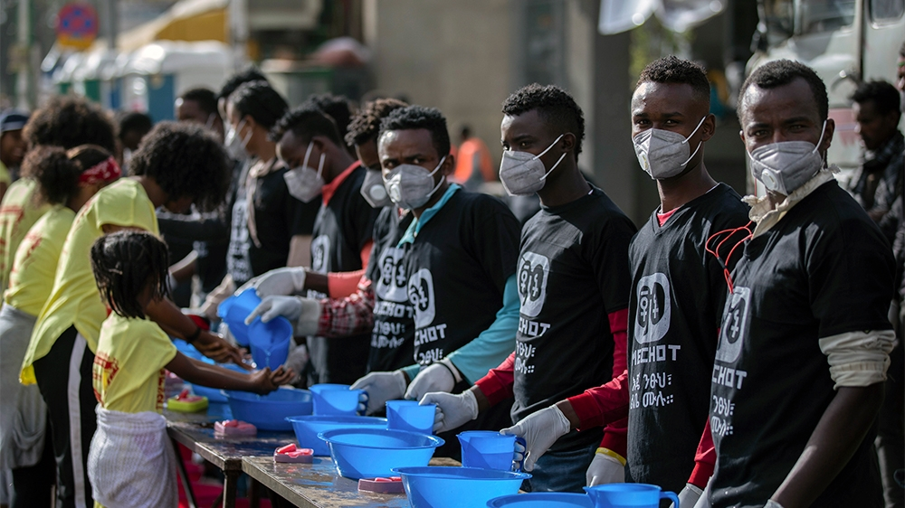 Volunteers stand ready to provide soap and water for participants to wash their hands against the new coronavirus at a women's 5km fun run in the capital Addis Ababa, Ethiopia Sunday, March 15, 2020.
